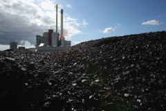 NEUMUENSTER, GERMANY - AUGUST 3:  The coal and garbage burning power plant of Statdtwerke Nuemuenster stands behind a mound of coal August 3, 2007 in Nuemuenster, Germany. The plant, which formerly relied solely on coal, is now equipped with a specialized furnace that allows the plant to produce two-thirds of its energy with garbage, which it receives from a local garbage processing center. The center, known as a Mechanisch-Biologisch Abfallbehandlungsanlage (MBA), or Mechanical-Biological Waste Processing Center, converts 55% of the garbage it receives into high-energy fuel, which it then sends to the city's converted power plant. The plant's management cites the twofold environmental benefit of burning the garbage, namely that it prevents the emission of methane gas from the biodegradation of the garbage (methane gas is 21 times more potent at warming the earth's atmosphere than CO2), and the reduced CO2 emissions from burning the garbage rather than coal.  (Photo by Sean Gallup/Getty Images)